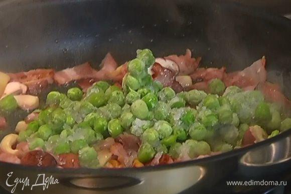 Когда бекон обжарится до золотистого цвета, снять сковороду с огня, добавить замороженный зеленый горошек и перемешать.