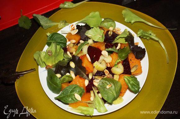 Немного остудим овощи. Режем свеклу такими же кусочками,как нарезана тыква. Выкладываем на тарелку овощи,присыпаем листьями салата и посыпаем орешками.