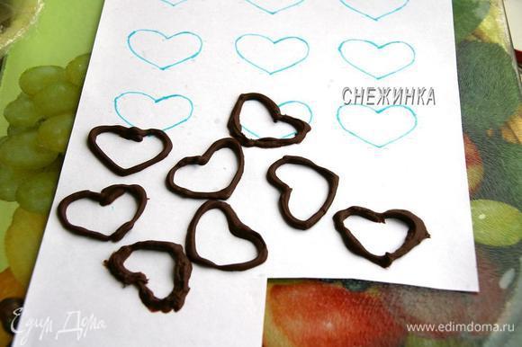 Подготовим украшения. Чтобы сделать сердечки из шоколада берём 40 г. шоколада, растапливаем его на водяной бане. Заготовим шаблоны сердечек. Я нарисовала сердечки на бумаге, положила лист на доску, а сверху накрыла пищевой плёнкой, хорошо закрепив края, чтобы плёнка не смещалась. Когда шоколад готов, перекладываем его в полиэтиленовый пакетик, отрезав кончик, и рисуем шоколадом по шаблону. Даём застыть в холоде. Сердечки легко отсоединяются.
