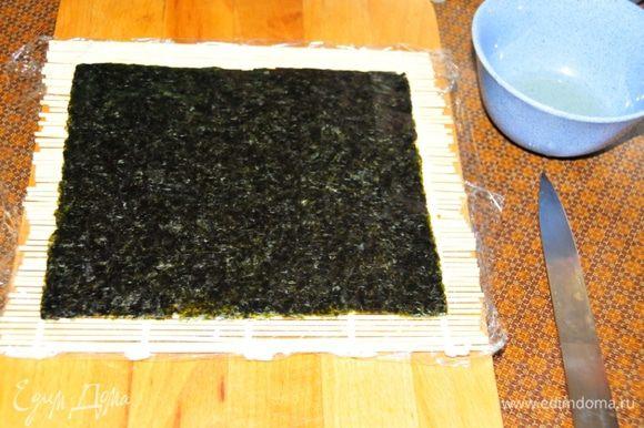 Начинаем делать роллы. Оборачиваем коврик для приготовления роллов пищевой плёнкой. Кладём его на стол. Сверху укладываем лист сушёных водорослей – нори.