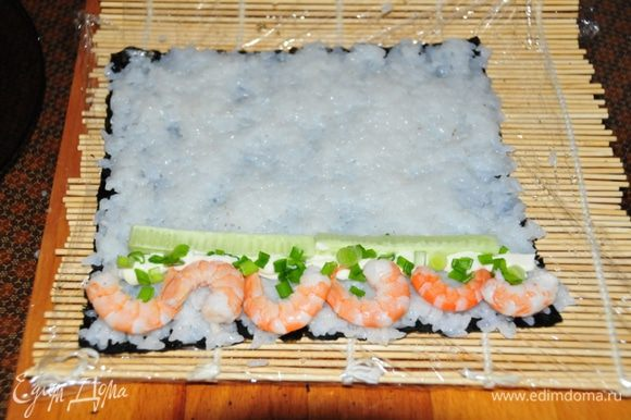 Второй ролл - Футомаки с креветками: Как и в первом случае на нории выкладываем рис. С краю начинка: креветки, тонкая полосочка майонеза, зелёный лук и брусочки огурчика. Сворачиваем точно так же. И разрезаем на 8 частей.
