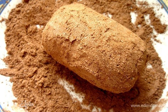 Смешать сахарную пудру и какао. Обвалять в этой смеси пирожное.
