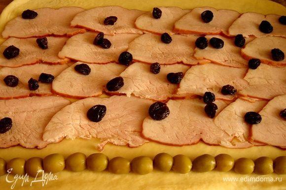 Раскатать тесто в прямоугольник. У края выложить в ряд оливки. На остальное тесто,отступив от другого края 10 см, разложить ветчину, поверх ветчины одной полосой выложить пластинки бекона и разбросать отжатый изюм. При желании можно повторить ряд оливок. Свернуть тесто в плотный рулет, начиная с оливок,оставив незавернутыми 10 см теста.