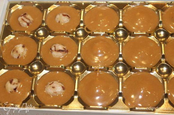 Формочки смазать маслом (можно растительным) и заполнить их расплавленным ирисом. В каждую конфетку в центр вставить по одному целому ореху (орехи предварительно нужно очистить от шелухи) и покрыть снова ирисом