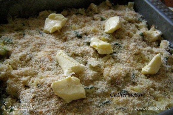 Форму смазать маслом. Выложить смесь. Сверху присыпать панировочными сухарями. разбросать кусочки масла.