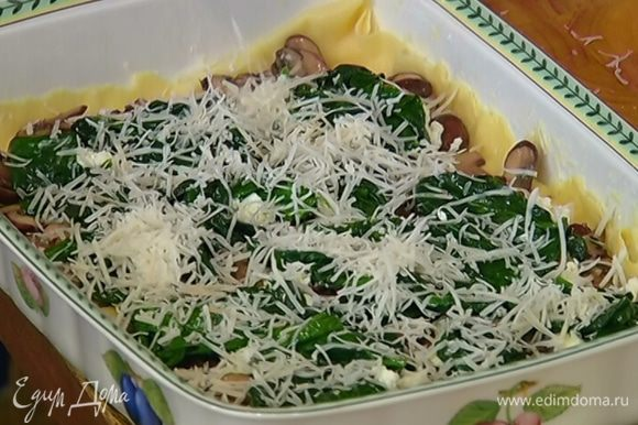 Выложить сверху еще пласты теста и повторить очередность слоев — грибы, мягкий козий сыр, шпинат, натертый твердый козий сыр.