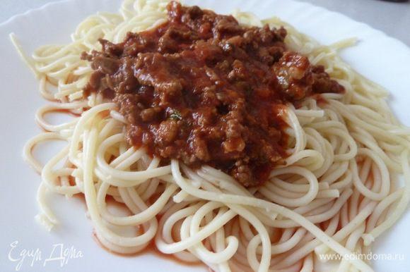 Лук обжаривается на масле и добавляется фарш, всё это жарится вместе. В это время в кастрюле нужно сделать томатный соус: томатная паста или/и кетчуп, можно добавить воды, чтобы соус был менее густым. Перчим, солим, в конце добавляем базилик, петрушку, чеснок. Пережаренный фарш выкладывается в кастрюлю с соусом и перемешивается