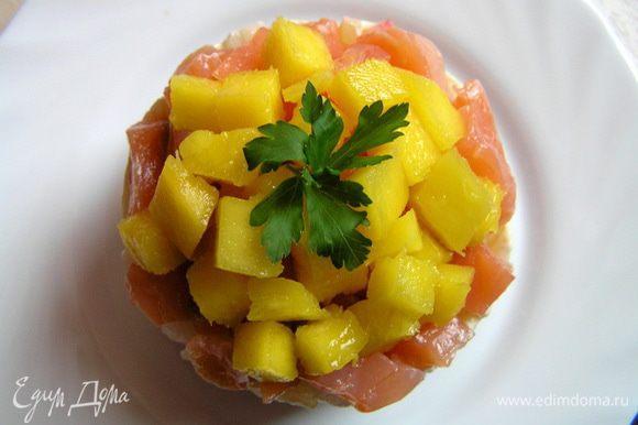 Перед подачей аккуратно снять кольца, сверху разложить нарезанный на маленькие кусочки манго, украсить петрушкой.