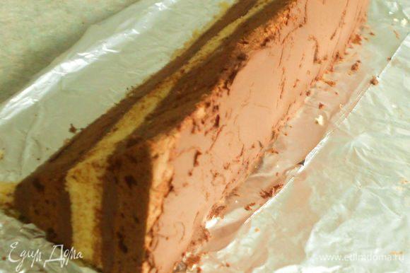 Переложить на фольгу одну часть так, чтобы шоколадный корж был вертикально, а разрезанная поверхность снаружи. Намазать ножом на шоколадный корж 4 ст.л. ганаша,