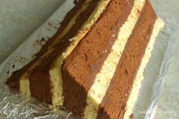 ...приложить к нему вторую половину светлым коржом, а разрезанной стороной кнаружи. Нежно прижать половинки друг к другу. Теперь пирог имеет форму большого треугольника.