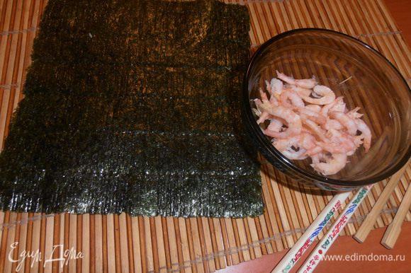 Продукты не успела сфотографировать, только вовремя шаги запечатлела... Вынимаем из пачки (у нас по 10 шт. продают) лист морских водорослей и кладём на бамбуковый коврик блестящей стороной вниз. Можно сбрызнуть рисовым уксусом.