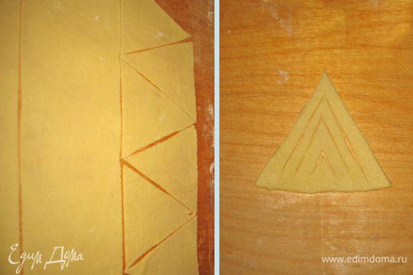 Тесто раскатать толщиной 3-4 мм и разрезать на равносторонние треугольники со сторонами примерно 10-11 см. На каждом треугольнике сделать надрезы как показано на фото.