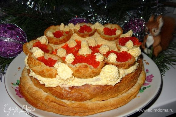 На застывшую поверхность торта нанести узоры из маскарпоне и красной икры. Маленькие эклерчики тоже украсить красной икрой.