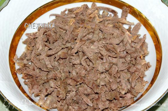 Нарезаем отварную говядину небольшими кусочками и укладываем в глубокую миску.
