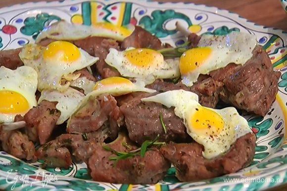 Готовое мясо посыпать листьями розмарина, выложить на мясо глазунью из перепелиных яиц и подавать с салатом.