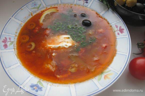 Довести бульон до кипения, положить вареное мясо, заправку из жареного лука с копченостями и томатом, огурцы. Варить 8–10 мин. на маленьком огне. В конце варки добавить каперсы, соль по вкусу - если потребуется. У меня вместо каперсов были оливки, фаршированные каперсами. Снять с огня, дать настояться 10- 20 мин. Солянку разлить по тарелкам, положить в тарелки по несколько черных оливок, 1-2 тонких дольки лимона. Посыпать порезанной зеленью петрушки. В соуснике поставить сметану.