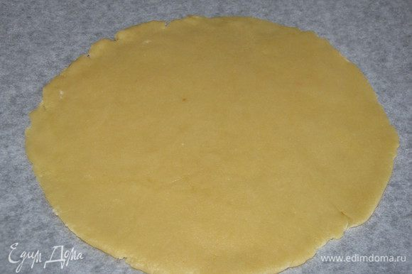 Достать тесто из холодильника, разделить на две неравные части. Большую часть раскатать в круг и перенести на противень, застеленный пекарской бумагой.