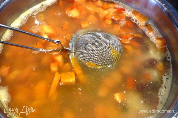 Рис зальем оставшимся бульоном, добавим морковь, сладкий перец, изюм, куркуму и кардамон, положенный в ложку для заваривания чая, также положим палочку корицы, нагреем до кипения и оставим вариться на 10 минут под крышкой на медленном огне. Снимем с огня, достанем кардамон и корицу, перемешаем и оставим под крышкой на 10 минут «париться» до готовности.