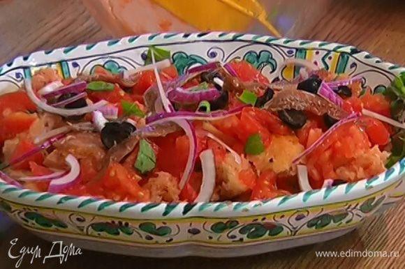 Сверху на салат выложить оставшиеся помидоры и базилик, оливки, анчоусы, красный лук. Все перемешать и сразу подавать.
