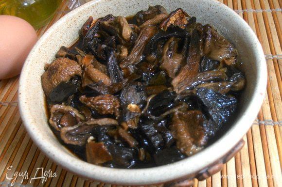 Через 2-3 часа сливаем тёмную жидкость (можно использовать в суп!) и отжимаем грибочки.