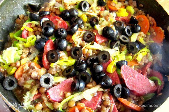 Добавить маслины, приправить свежемолотым чёрным перцем, аккуратно перемешать.