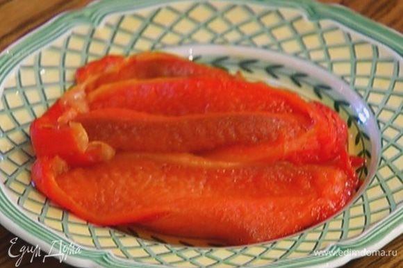 Сладкий перец запечь в духовке, затем снять кожицу и нарезать мякоть длинными, широкими полосками.