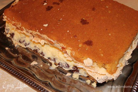 теперь нам надо одну часть пирога, где мак, смазать половиной крема, а другую часть мы переворачиваем и кладем серединой внутрь. Пирог очень хрупкий, поэтому, чтобы не поломать, мы под вторую часть подкладываем доску разделочную и вместе с ней перевернем.