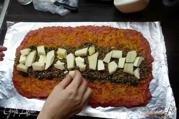 У меня пропадала отварная гречка, поэтому она пошла следующим слоем. На гречку выложила кусочками сливочное масло, чтобы не было сухо. Добавила порезанный брусочками сыр, у меня была моцарелла для пиццы. Начинка готова!
