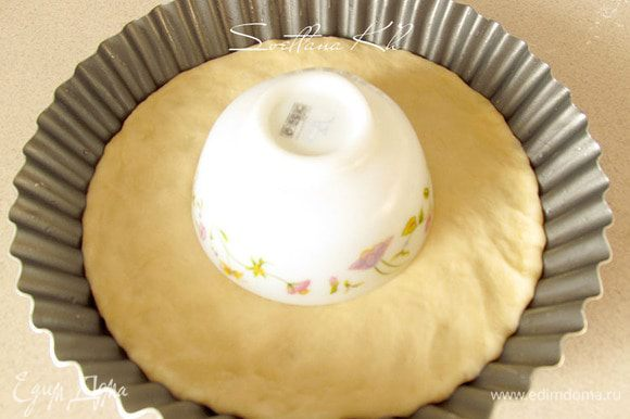 Выложить лепешку в смазанную форму, где будете выпекать пирог. Наметить центр круга и положить в круг перевернутое блюдце или пиалу. Там будет другая начинка.