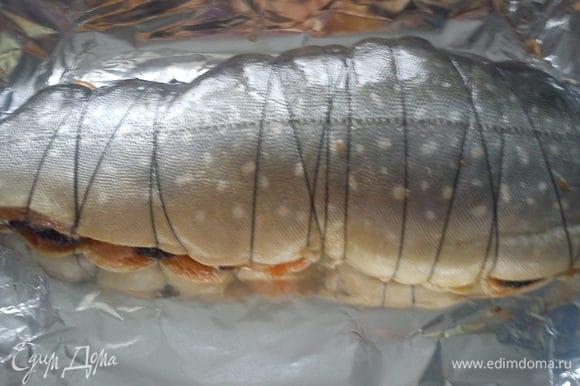 Перевязать рыбу пищевой ниткой и обмазать маслом от помидор. Выложить на лист для запекания. Запекать в духовке при 200 С 45 минут.