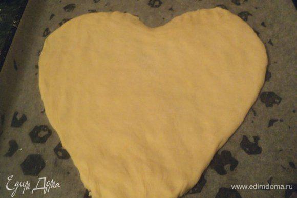 Дрожжевое тесто разделить на две части, одну часть немного меньше другой. Меньшую часть теста раскатать в пласт толщиной 1 см и вырезать сердце. Выложить на противень, смазанный маслом.