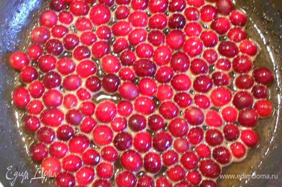 В масло на сковороде всыпать ягоды, добавить сахар и карамелизировать 1 мин, затем влить апельсиновый сок и выпарить жидкость наполовину. Влить коньяк, фламбировать, снять с огня и накрыть крышкой.