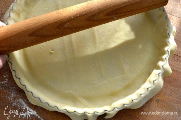 Скалкой пройтись по краю формы и обрезать лишнее тесто (или сделать это просто ножом)