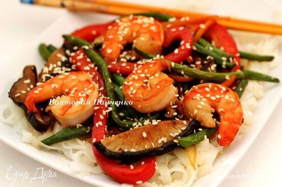 """Сделать на тарелке """"подушку"""" из рисовой лапши, на нее выложить обжаренные овощи и креветки, посыпать кунжутными семечками и немедленно подавать. Приятного аппетита!!!"""