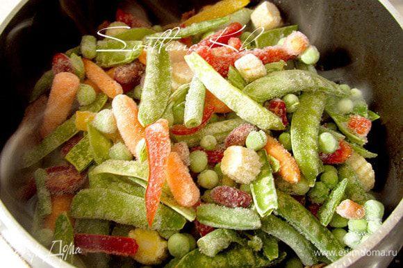 К мясу добавить смесь замороженных овощей, посыпать красным перцем. Тушить до полуготовности.