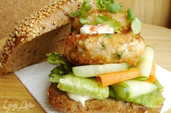 Булки разрезать , нижнюю часть смазать соусом. Выложить на каждую булку по листу салата, ломтики огурца и моркови, по 2 рыбные котлетки. Смазать котлетки соусом, украсить оставшимися веточками кинзы и накрыть верхней частью булки. Приятного аппетита!