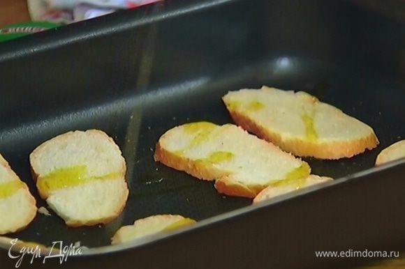 Багет тонко порезать, поместить в небольшой противень, слегка сбрызнуть оливковым маслом и отправить в разогретую духовку на 5 минут.
