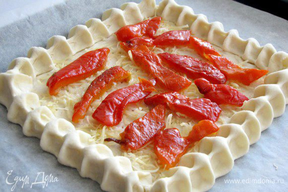 Выложить на тесто кусочки запеченных перцев.