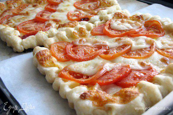 На них выложить по диагонали помидоры и моцареллу. Поставить в духовку на 15 минут. Готовый пирог посолить, поперчить, украсить базиликом.