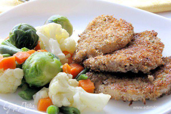 Выложите на тарелку горячие отбивные, гарнируйте их овощамии. Приятного аппетита!