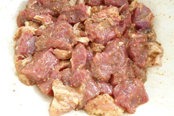 Мясо нарезать небольшими кусочками,добавить горчицу,соевый соус,виноградный уксус,смесь хмели-сунели,оливковое масло,все хорошо перемешать,накрыть крышкой посуду с мясом и оставить мариноваться на 1 час.