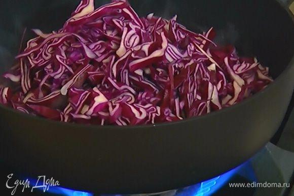 Разогреть в глубокой тяжелой сковороде оливковое масло, добавить капусту, лук, чеснок и обжаривать все пару минут.