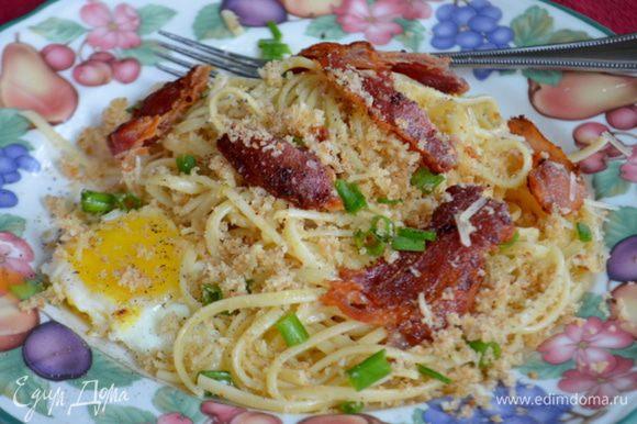 Разделить спагетти на 4 блюда.Также с беконом и яйцами,сверху посыпать хлебной крошкой из духовки,зеленым луком,пармезаном и посолить,поперчить по вкусу. Приятного аппетита.