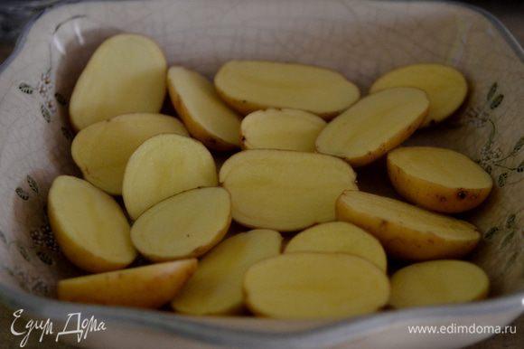 Разогреть духовку на 180 гр. Порезать картофель на половинки и выложить в жаропрочное блюдо.