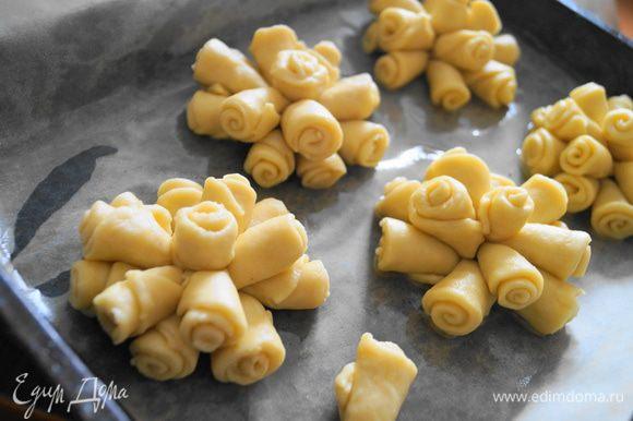 Доделываем из всего теста розы. И выкладываем их на противень застеленный бумагой для выпечки и смазанный немного маслом.