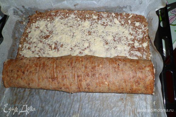 На горячий печёночный корж высыпать сыр, равномерно распределить по всей поверхности и свернуть в рулет и поставить в духовку еще на 5 минут.
