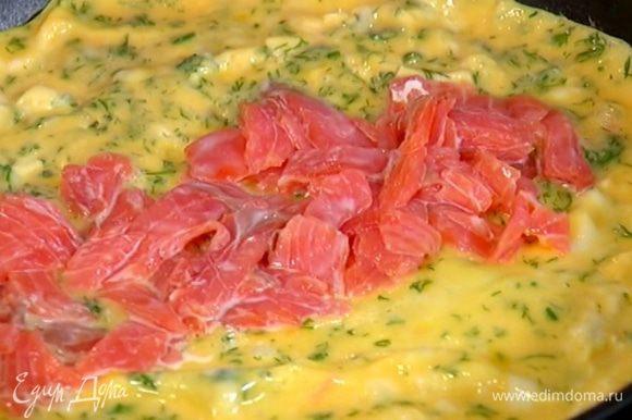 Когда омлет будет практически готов, в центр выложить форель и с помощью лопаток завернуть на рыбу сначала один край омлета, затем второй.