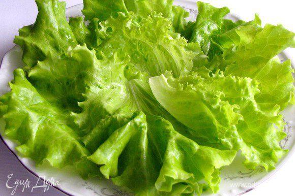 Выложить слой салатных листьев на плоское блюдо.