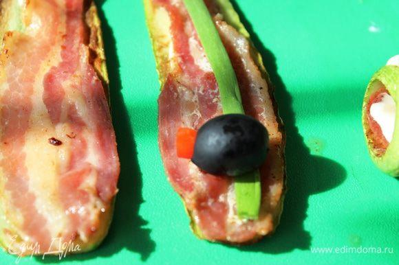 По центру разместить половину перышка зеленого лука, на него с одного края положить сюрприз: это может быть оливка без косточки, в центр которой необходимо поместить кусочек яркого болгарского перца...