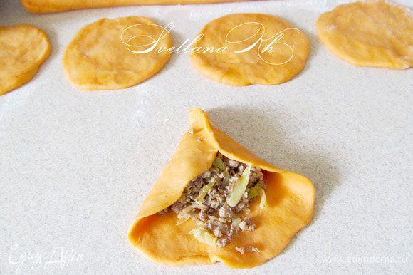 Тесто разделить на 2 части для удобства в работе. Из каждой части скатать колбаску, а затем нарезать ее на кусочки. Из кусочков раскатать лепешки, выложить на них начинку и защипать края. Пирожки выложить швом вниз на противень. Смазать водой и посыпать кунжутом. Выпекать 20-15 минут при 180 гр. Подавать с острым соусом.